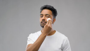 man applying toner on face